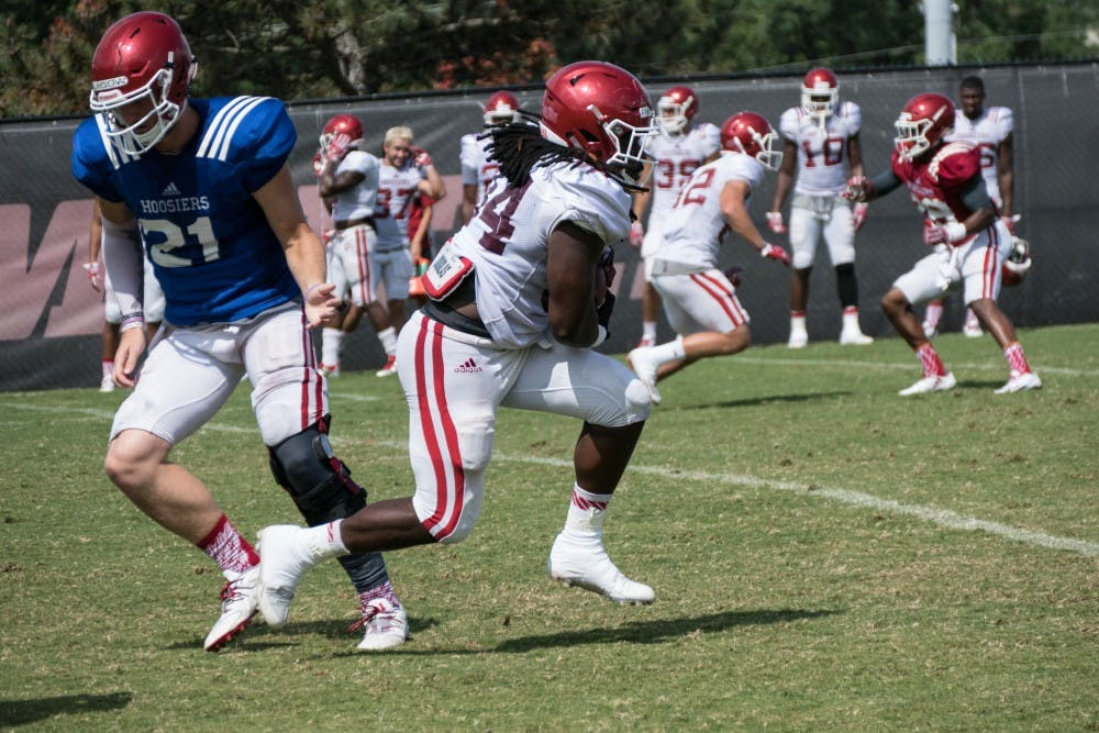 Junior running back Devine Redding receives a handoff from junior quarterback Richard Lagow during an IU fall camp practice.