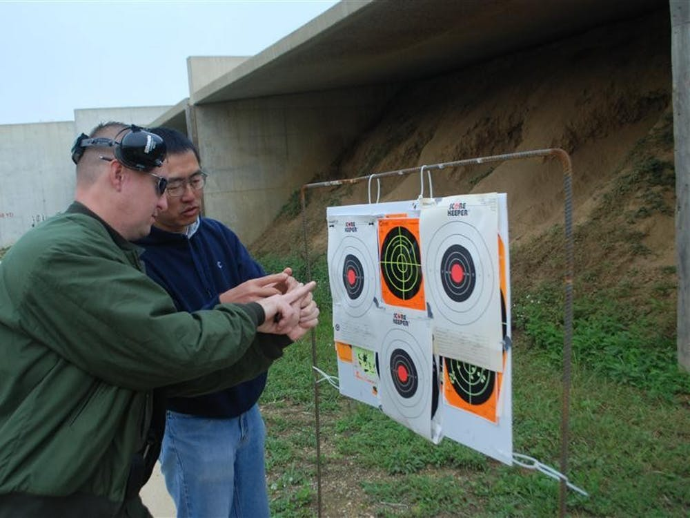 Conservation Officer Bryan Knoy of the Department of Natural Resources instructs Hunt, Fish, Eat participant Xigang Li on Sept. 29 at Atterbury Shooting Range. Knoy and other DNR staff taught participants how to catch and prepare their own food.