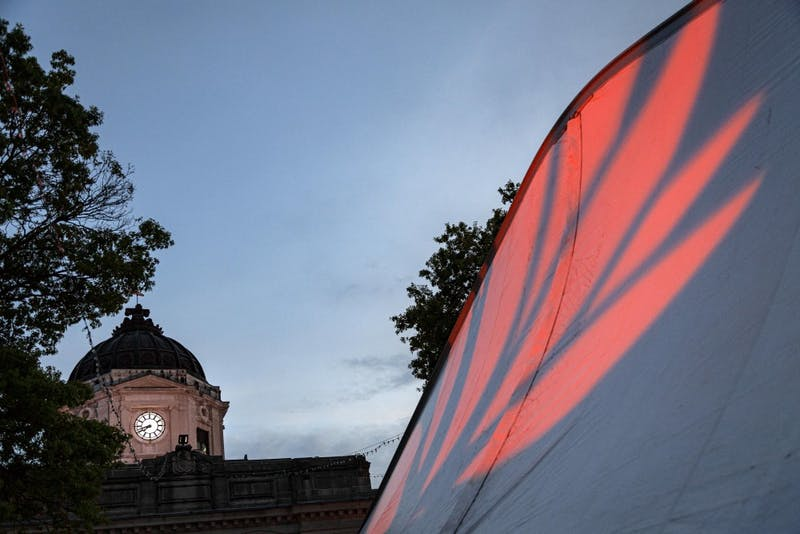 The Monroe County Courthouse can be seen while a projection of a lotus flower lights up the outside of a tent Sept. 28 on Sixth Street during the 2019 Lotus World Music & Arts Festival. The festival is part of the Lotus Education & Arts Foundation and is one of the oldest world music festivals in the U.S.