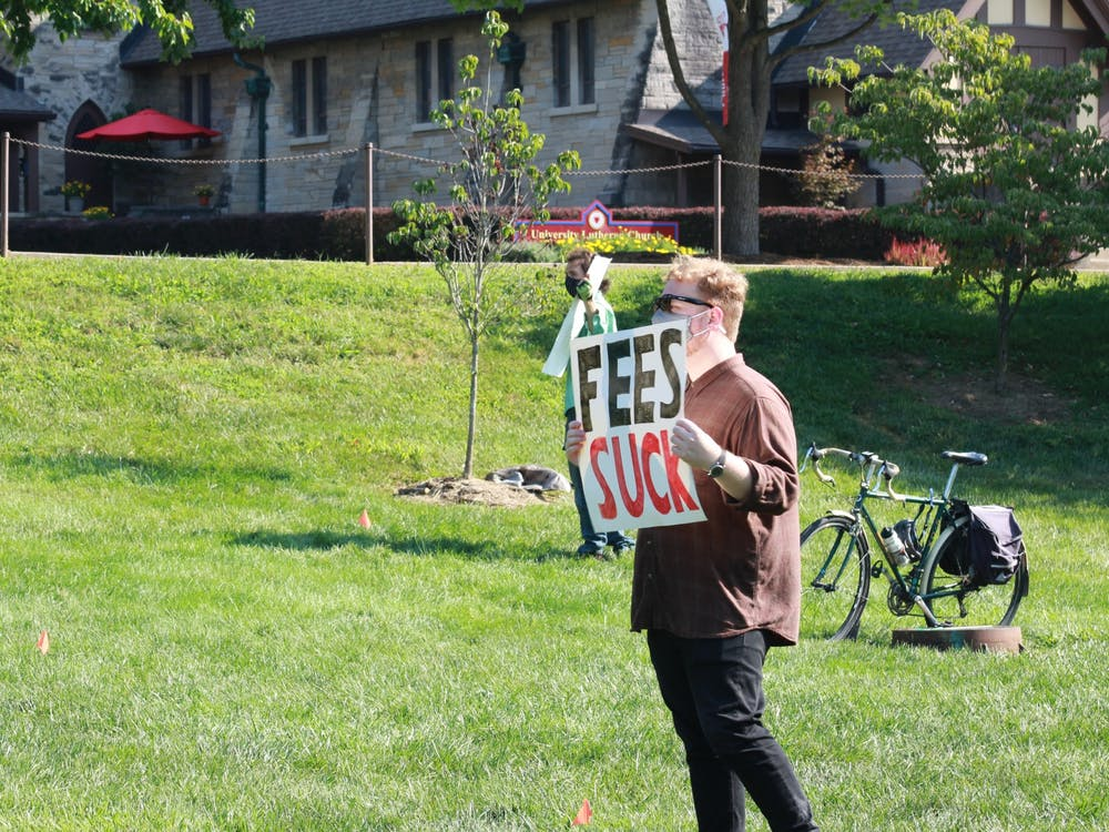 """A protester holds a sign that says """"Fees suck"""" during a protest Aug. 24, 2020, in Dunn Meadow. IU Provost Lauren Robel sent a 14-page letter to graduate workers Feb. 19 addressing some of the concerns made by IU's Graduate Workers Coalition."""