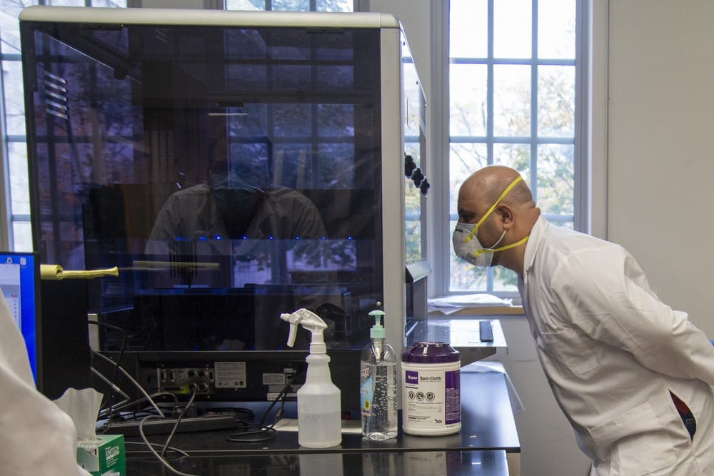 <p>Lab technician Ahmed Alazawi watches as a Hamilton STARlet robot transfers saliva samples into 96-well plates Oct. 27 in IU's COVID-19 testing labs in Myers Hall. The machine is the first transfer of testing samples into smaller well plates, which can hold 96 samples. This robot is on loan from the Eli Lilly corporation in Indianapolis and another machine is due for delivery before Thanksgiving, scientific director Craig Pikaard said.</p>