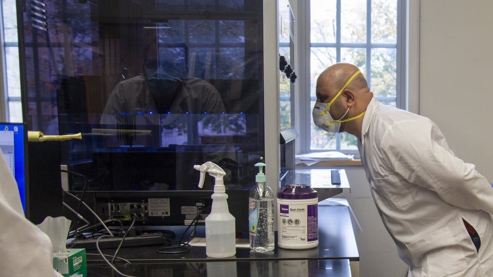 Lab technician Ahmed Alazawi watches as a Hamilton STARlet robot transfers saliva samples into 96-well plates Oct. 27 in IU's COVID-19 testing labs in Myers Hall. The machine is the first transfer of testing samples into smaller well plates, which can hold 96 samples. This robot is on loan from the Eli Lilly corporation in Indianapolis and another machine is due for delivery before Thanksgiving, scientific director Craig Pikaard said.