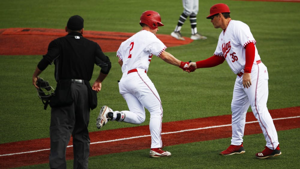Then-sophomore Cole Barr rounds third base and shakes hands with Coach Dan Held on April 3, 2019, at Bart Kaufman Field. IU will play Purdue on Wednesday in Bloomington.