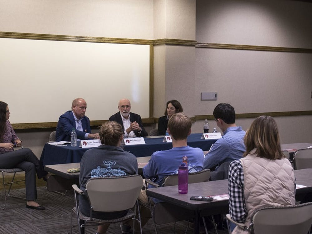 Charles J. Clifford (second-right), a co-founder of Tumi, Inc., who shared his working experience in the front of students on Monday afternoon in the Maple Room.