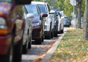 Parked cars are lined up against the curb on E. 6th St. There have been a rash of car break-ins and thefts recently.