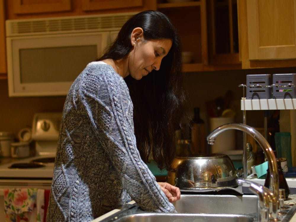 Paola Carmona washes a pot used earlier in the evening. She said her husband Gustavo is the real cook of the family, so she tends to stick to dishes.