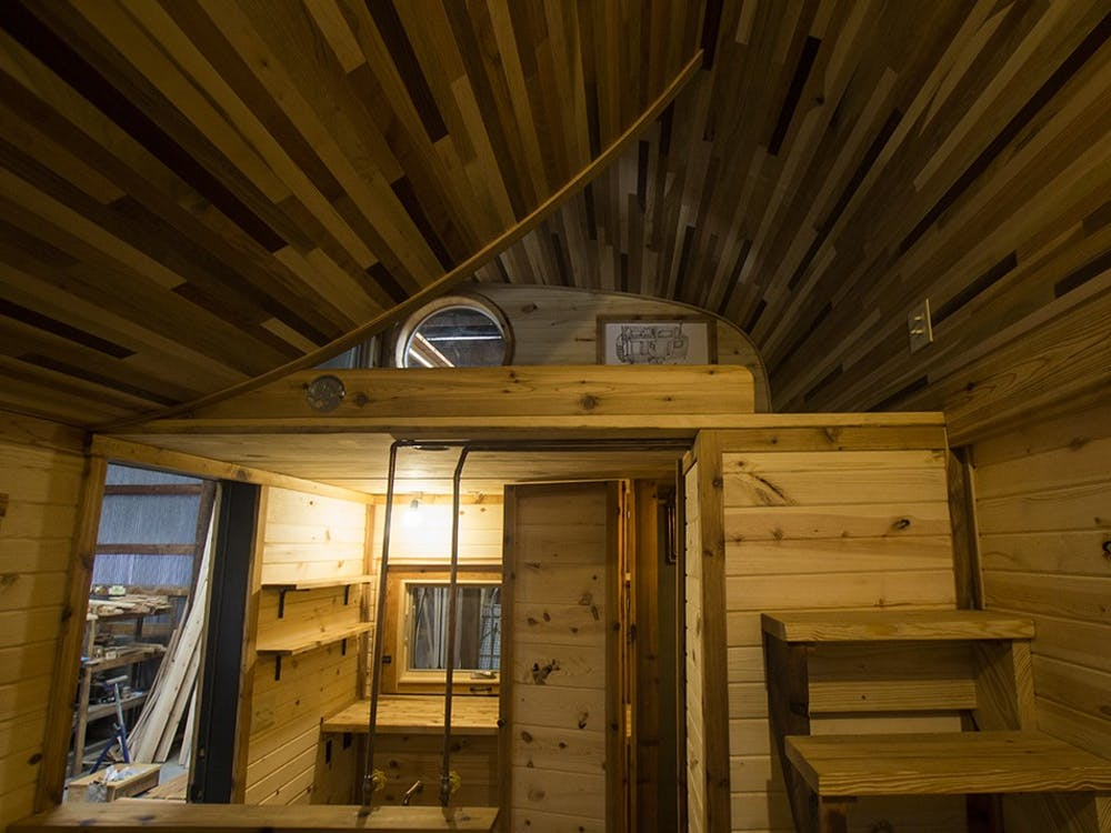 The main interior space of the tiny house holds a tiny stove, tiny sink and regular-sized bathroom. The project was commissioned to be placed on a southern Indiana farm and can be both mobile and permanently set.