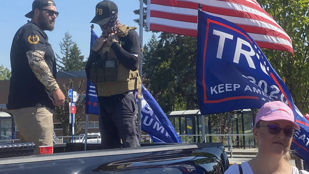 Men wearing symbols of Proud Boys, a violent right-wing extremist group, stand watch as supporters of President Donald Trump kick off a truck caravan near Portland, Oregon.