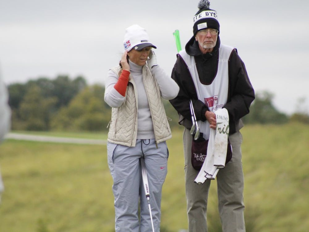 Senior professional golfer Jackie Gallagher-Smith talks with her caddy about her upcoming putt on hole 15 at the Pete Dye Course in French Lick, Indiana.