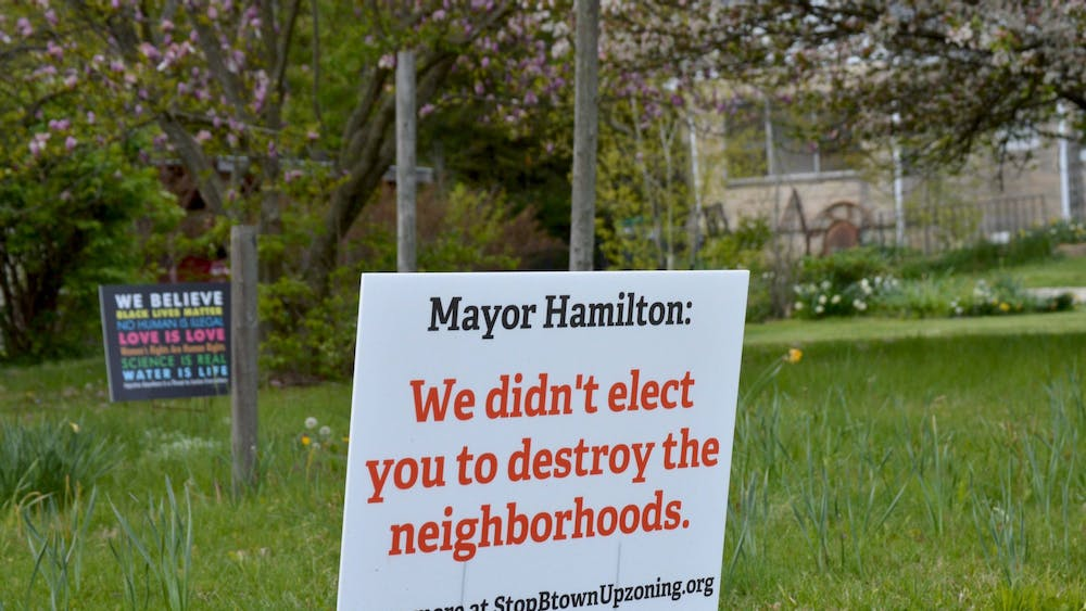 "A sign near Bryan Park reads ""Mayor Hamilton: We didn't elect you to destroy the neighborhoods."" The Bloomington City Council voted down a proposed amendment Tuesday rejecting the Plan Commission's recommendation to allow duplexes in single-family home neighborhoods."