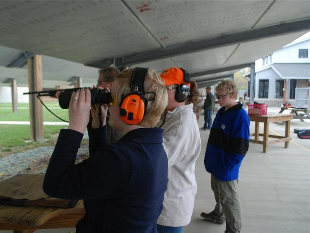 Meg Nickless, a master's student in counseling psychology, looks at her target to find where she hit it Sept. 29 at Atterbury Shooting Range during Hunt, Fish, Eat. Participants in the Department of Natural Resources program learned skills necessary to catch and prepare their own food.