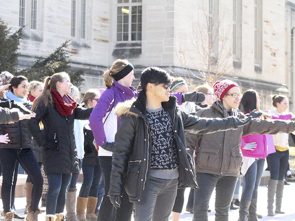 Kelvin Burzon, a first year graduate student studying for his MFA in photography, dances in front of the Sample Gates as part of a flash mob to raise awareness of sexual and domestic violence.