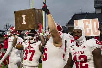 Sophomore running back Ahrod Lloyd holds up the box the holds the Old Oaken Bucket on Nov. 30 at Ross-Ade Stadium. IU won back the Oaken Bucket and defeated Purdue in double overtime 44-41.