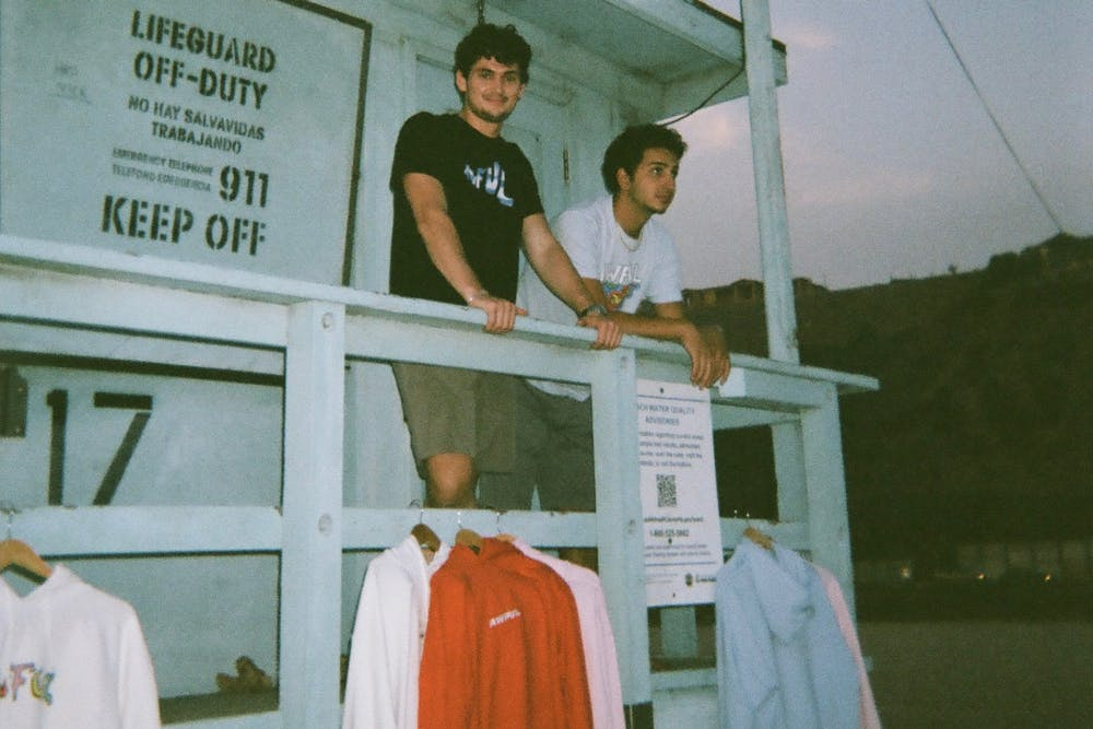 <p>Awful Cloth co-creators, Fordham University senior Emmitt Flynn and IU senior Charles Zayed, pose with their clothing in October 2020 in Santa Monica, California.</p>