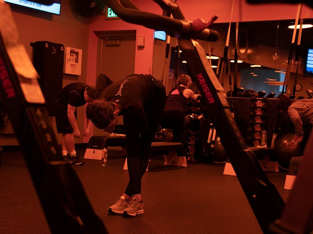 """After their workout, Head Coach Jean Sherfick leads members in a cool-down stretch. She tells them about upcoming Orangetheory events, including a difficult workout week, called """"Hell Week,"""" coming up the week of Halloween."""