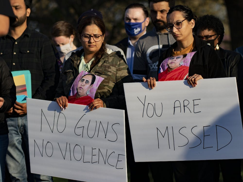"""Attendees of a vigil in honor of those killed April 15 at the FedEx Groud shooting in Plainfield, Indiana,hold signs Saturday at Krannert Park in Indianapolis. """"You are missed,"""" and """"No guns, no violence,"""" the signs read."""