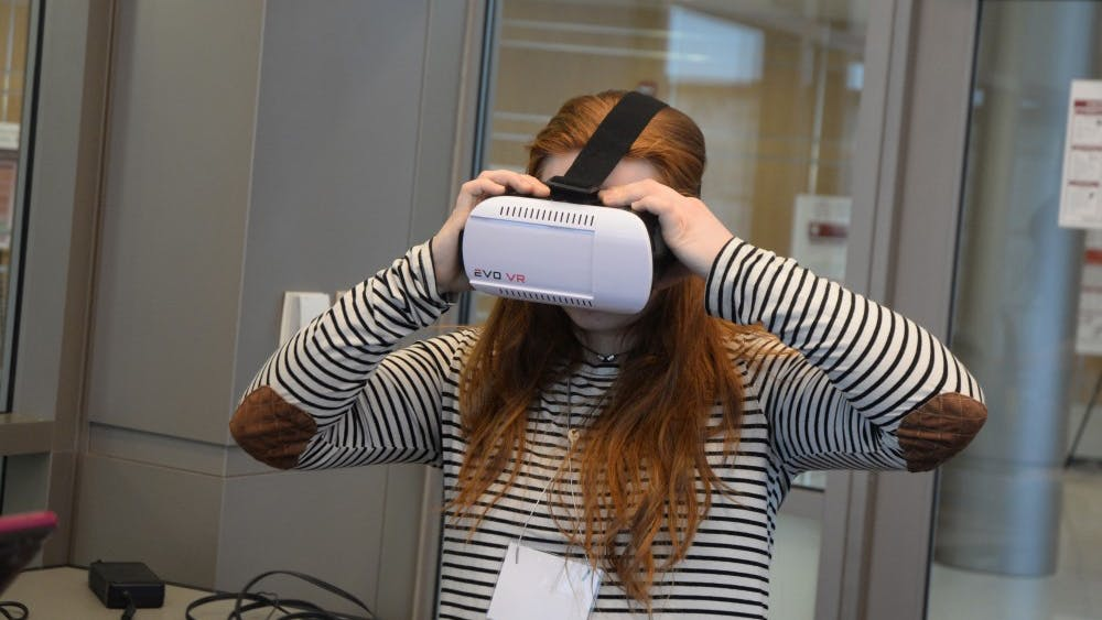 Freshman Faith Frazer tries on a Virtual Reality headset during the CEWiT Summit in Union Street Center. The Summit took place March 23 and 24 and was open for IU students and community members.