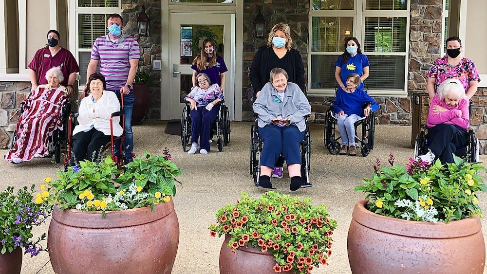Residents of the Autumn Hills Alzheimer's Special Care Center smile for a photo. The center received one of  14 iPads that University Information Technology Services donated to hospitals and nursing homes in Monroe County.