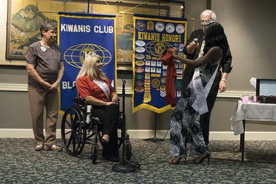 A'Niyah Birdsong, Miss Indiana University 2017,  presents an IU t-shirt to Lesamarie Hacker, Ms. Wheelchair of Indiana. Hacker spoke to the Kiwanis Club of Bloomington on Thursday.