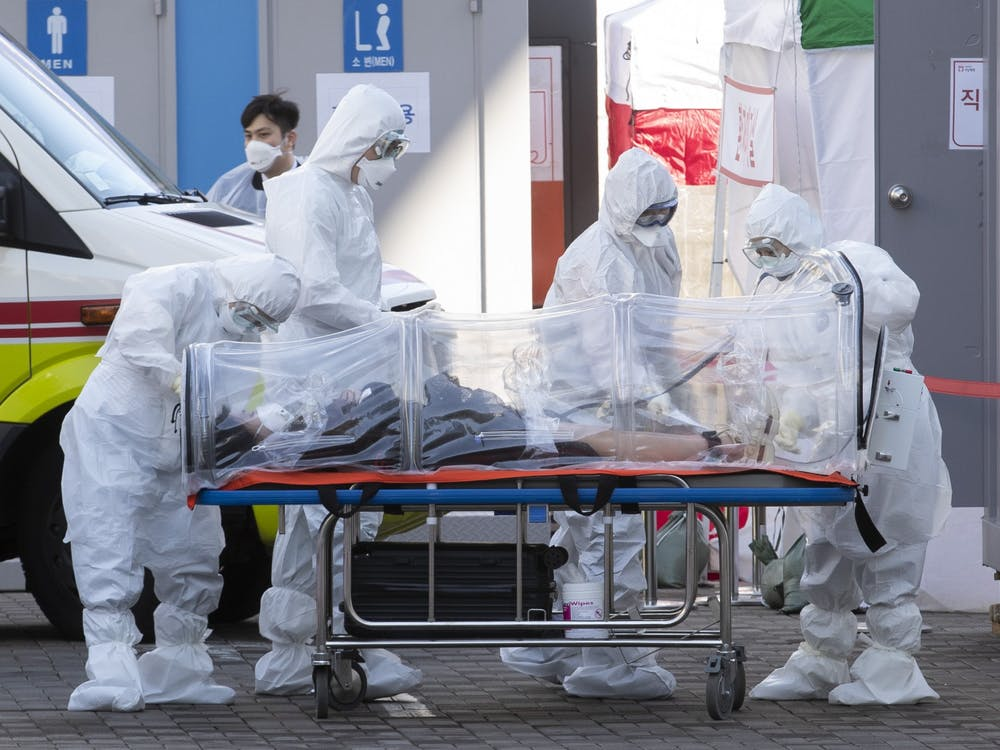 Medical workers transfer a patient to a hospital March 11 in South Korea.