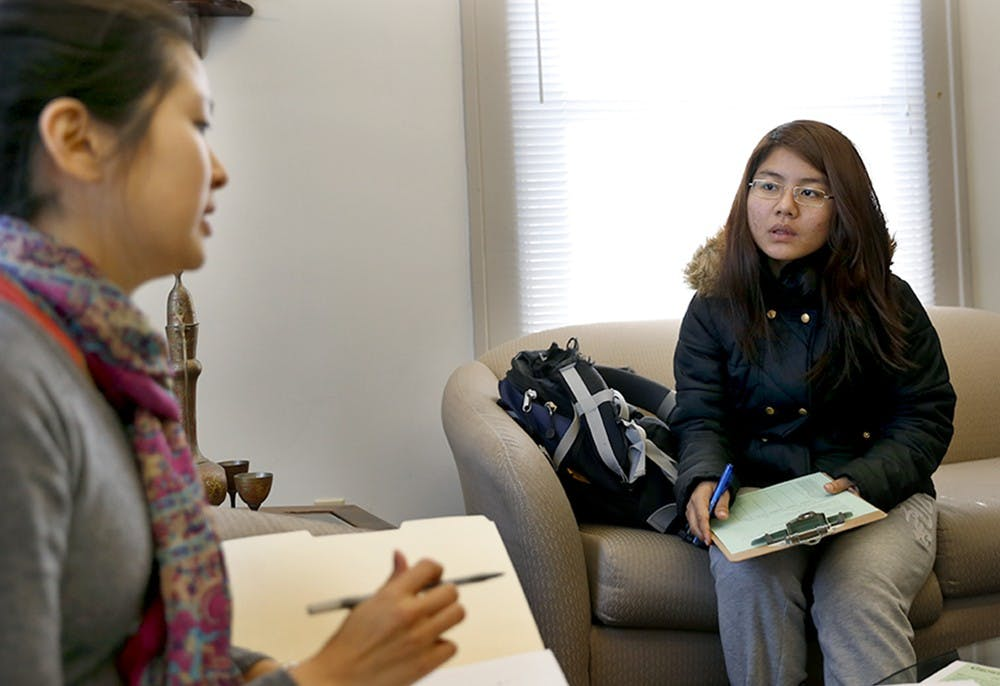 """Sarah Stamey, left, program associate, tells freshman Tang Mawi what role of a tutor is during a tutor orientation Tuesday at the Asian Culture Center. The Asian Culture Center has """"English Tutoring / Peer Support"""" program every semester to help international students for peer papers and cultural adjustment by student volunteers."""