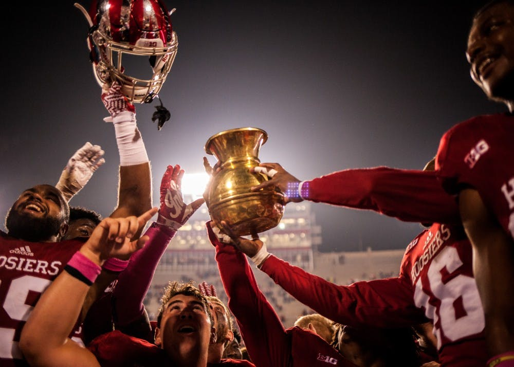 <p>Members of the Indiana football team raise the Old Brass Spittoon after defeating Michigan State 24-21 during an Oct. 2016 game. </p>