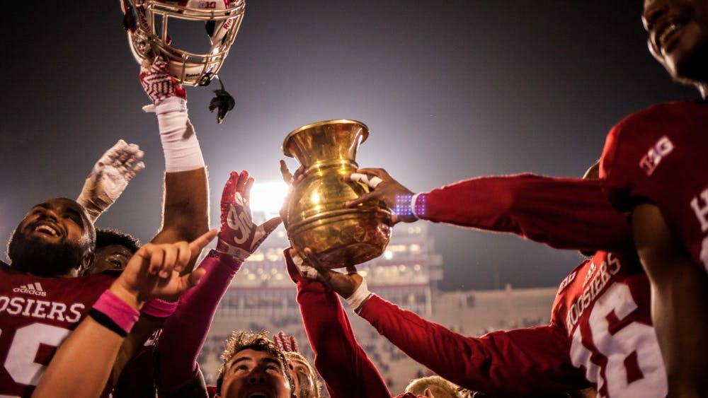 Members of the Indiana football team raise the Old Brass Spittoon after defeating Michigan State 24-21 during an Oct. 2016 game.