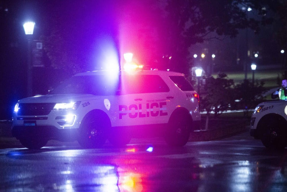 <p>Two police cars park at the intersection of 10th Street and Walnut Grove on Oct. 19 after an IU alert was sent. Authorities responded to a utility explosion underground nearby.</p>