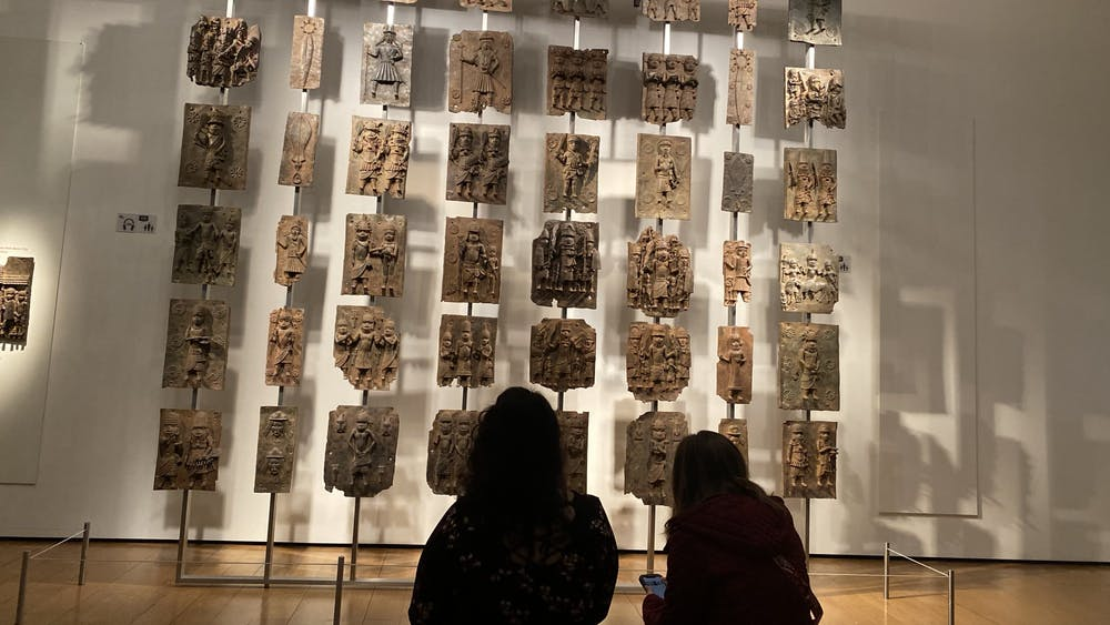 People look at the Benin Bronze statues Oct. 9, 2021, in the British Muesuem in London. The statues are a group of decorative plaques and commemorative heads that are made of ivory, leather, coral and wood.