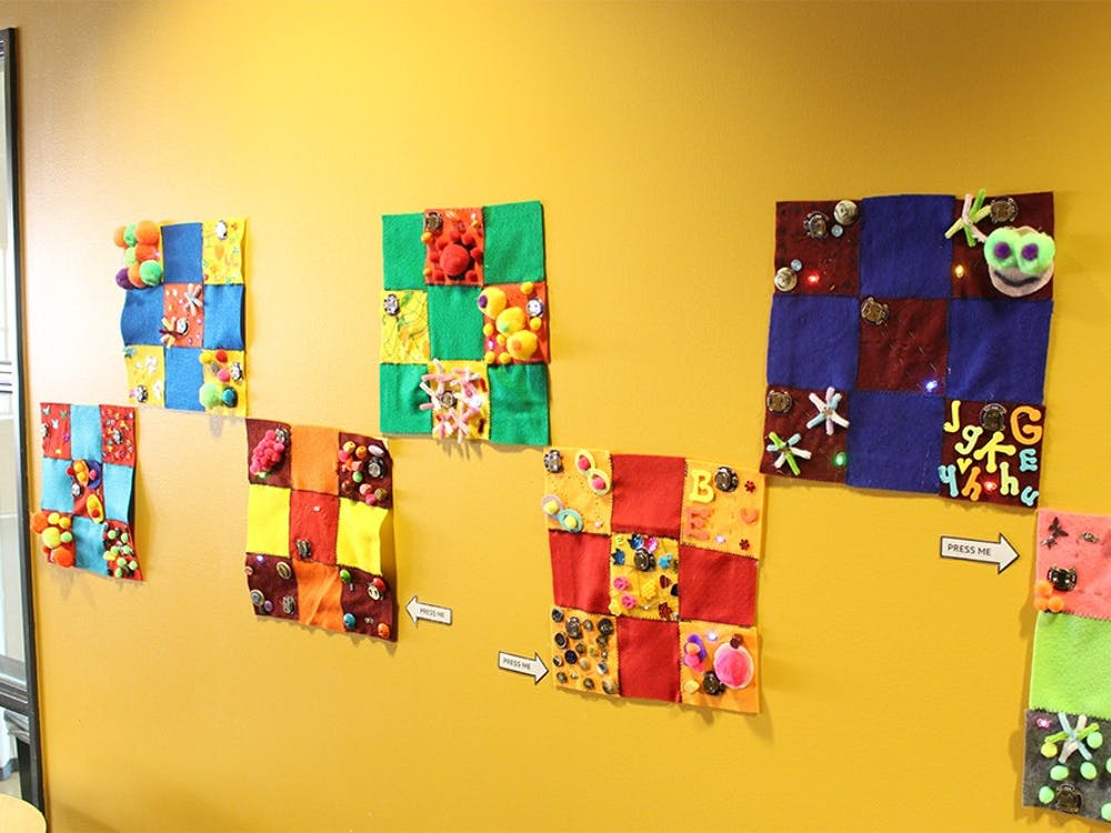 The E-Textile Community Quilt makers used fabric, conductive thread and lights to create their own patchwork pieces. They are on display in the WonderLab through March.