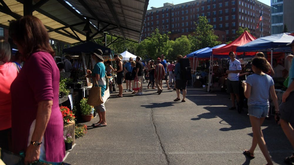People walk through the aisles of vendors at the Bloomington Community Farmers' Market near City Hall on June 16. A letter sent June 4 alleges a vendor at the market, Schooner Creek Farm, is owned by white supremacists.