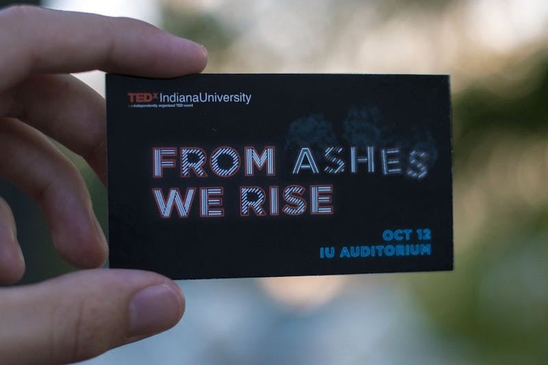 """A student holds an information card for an upcoming TEDxIU event. The event is titled """"From Ashes We Rise"""" and will take place Oct. 12 in the IU Auditorium."""
