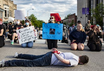"Protestor Michael Lang lays on the ground with his arms tied behind his back in honor of George Floyd on May 29 on College Avenue. ""What I did wasn't brave,"" he said. ""George Floyd didn't get to get back up."""