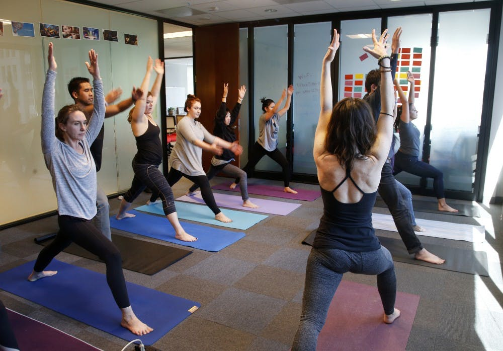 <p>A group of people do yoga. The SRSC has yoga classes available free for students.</p>
