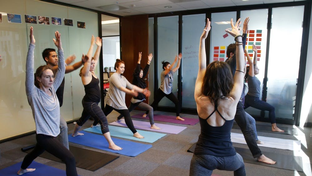A group of people do yoga. The SRSC has yoga classes available free for students.