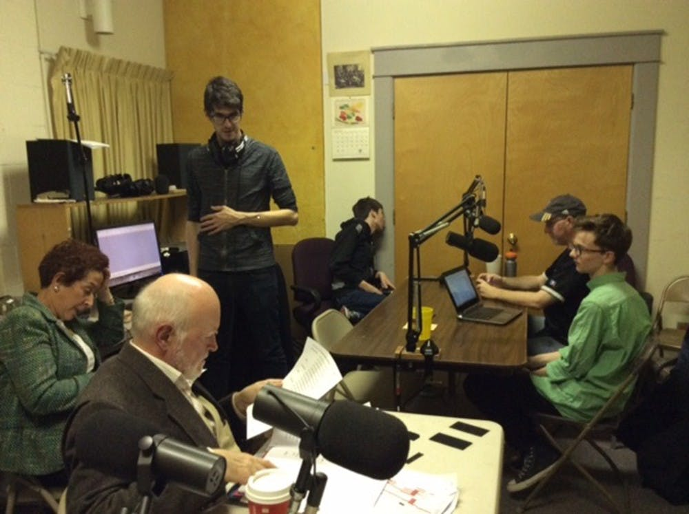 Members of the Monroe County Civic Theater prepare for a radio performance that will air on Christmas Day.