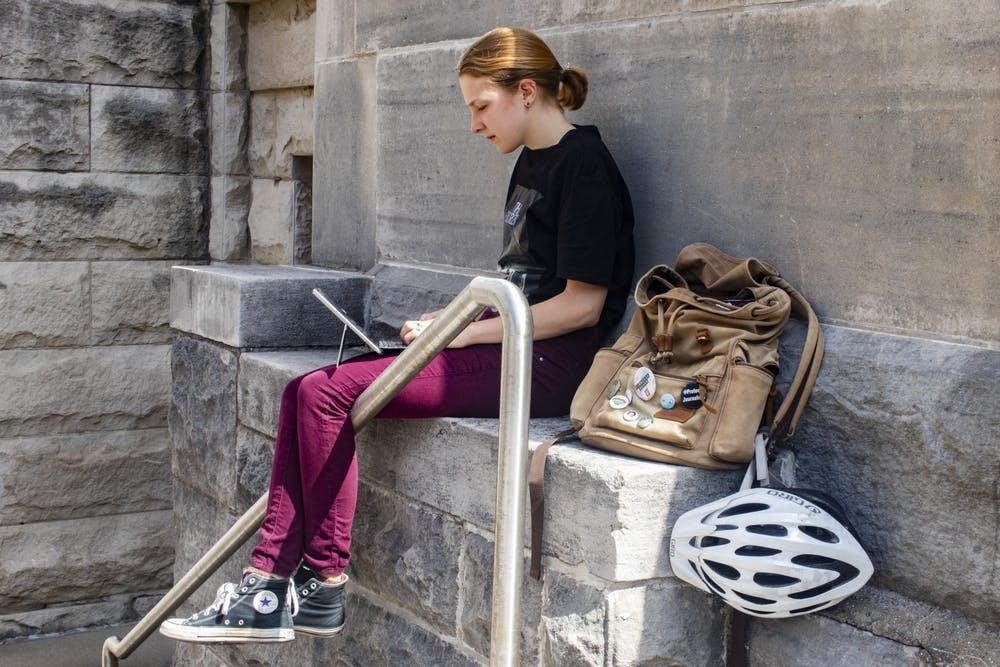 <p>Senior Arielle Pare uses her laptop on Sept. 17, 2019, outside Franklin Hall. IU Students say that they have been struggling only having online classes.</p>