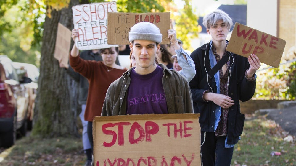 """Alex Johnson leads a group of protesters Oct. 18 along South Grant Street. He held a sign saying """"stop the hypocracy,"""" which refers to protesters alleging hypocrisy over IU Notify alerts for off-campus shootings over the past year."""