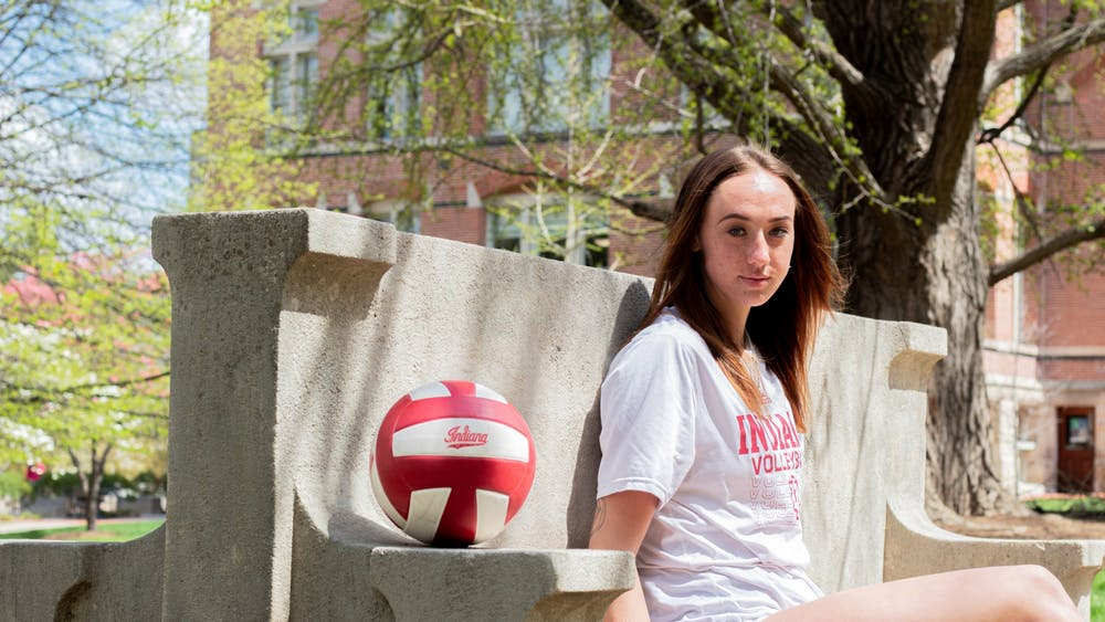 Junior outside-hitter Kari Zumach sits at a bench on IU's campus on April 15. Zumach has worked to learn more about mental health since her transfer to IU.
