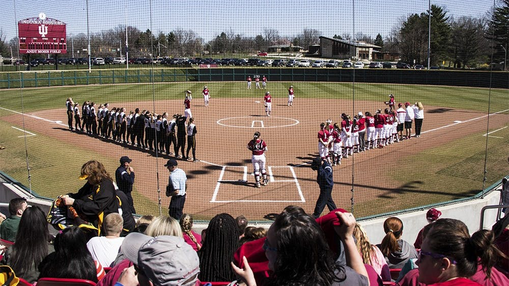 The IU and University of Iowa softball teams stand March 26, 2016, at Andy Mohr Field. The IU softball team spread #mightywithmicahon Twitter to welcome new graduate transfer Micah Schroder.