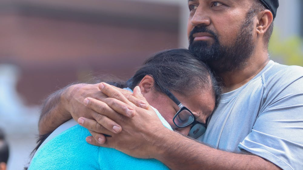Ramandeep Chochan cries into the chest of a loved one Sunday at Monument Circle in Indianapolis. Family members of victims killed in a mass shooting Thursday said that thoughts and prayers are not enough and demanded action going forward.