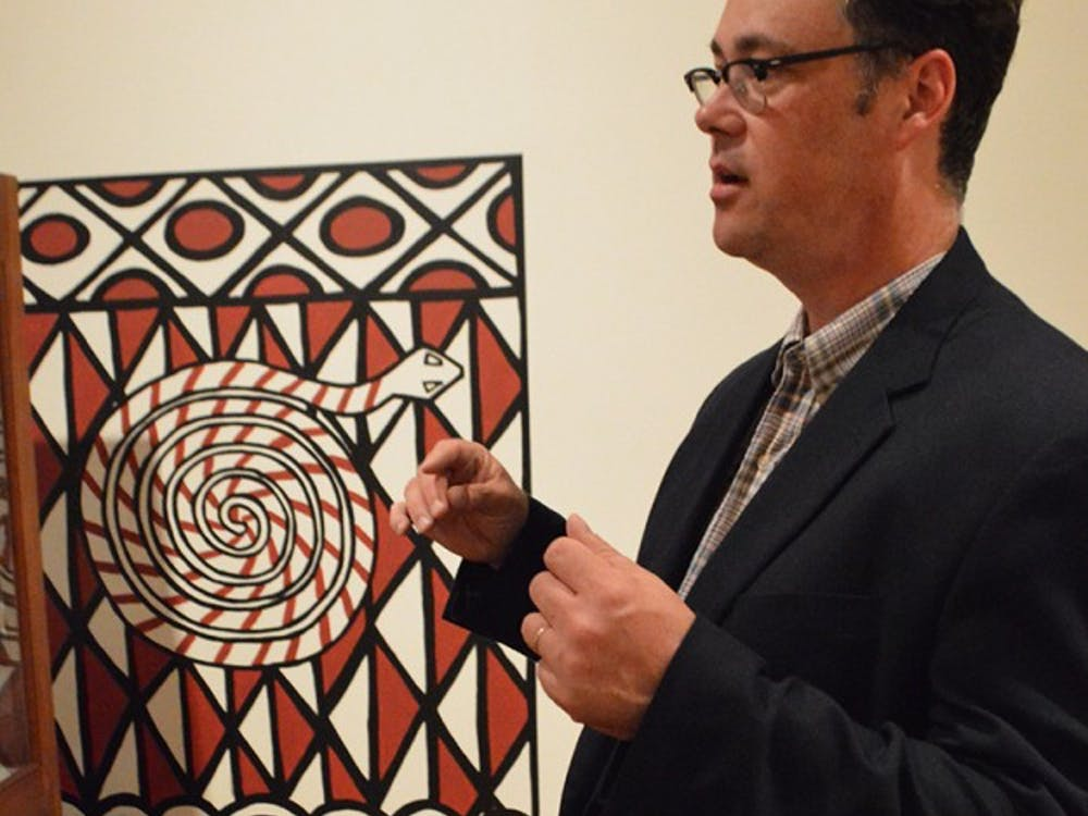 The Mathers Museum director Jason Baird Jackson explains the paintings featured on the wall. An artist based the paintings on how homes are painted in Ghana. This was an exhibit in Aug. 2014.