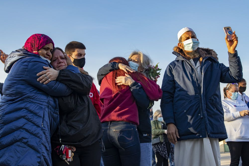 <p>Vigil attendees cry together Saturday at Krannert Park in Indianapolis. A candlelight vigil took place at 7 p.m. in support of families whose loved ones were victims of a mass shooting Thursday.</p>