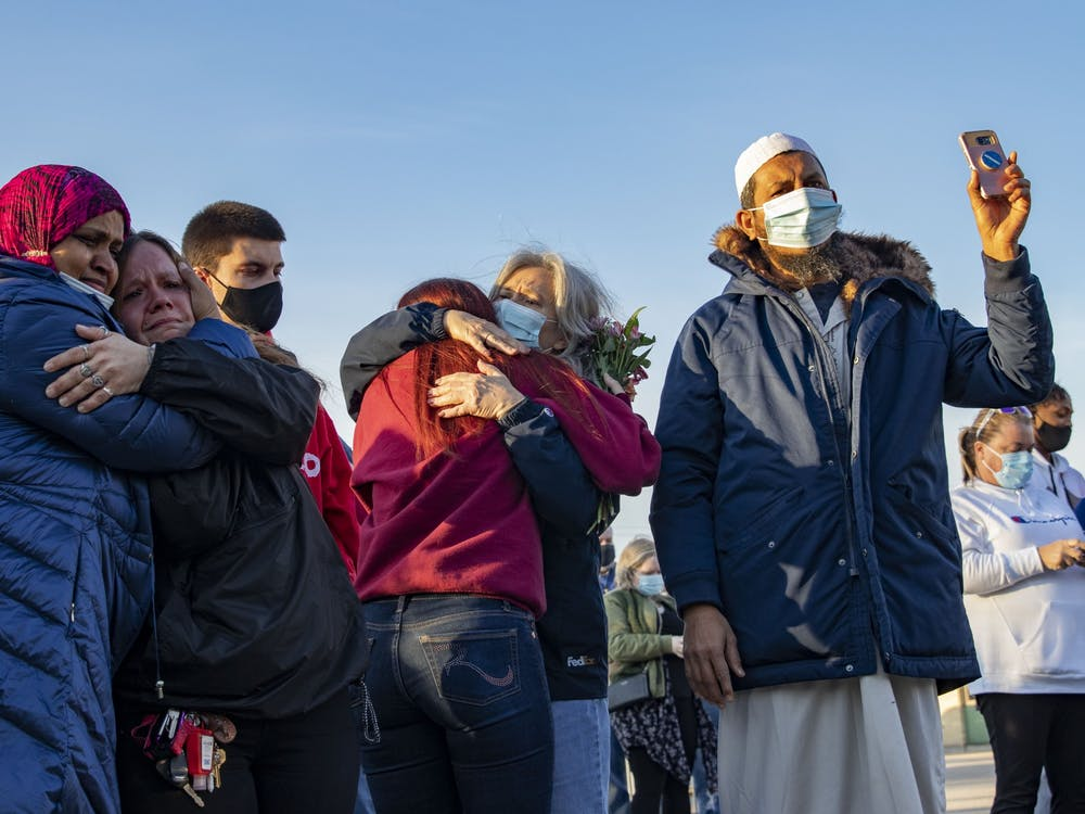 Vigil attendees cry together Saturday at Krannert Park in Indianapolis. A candlelight vigil took place at 7 p.m. in support of families whose loved ones were victims of a mass shooting Thursday.