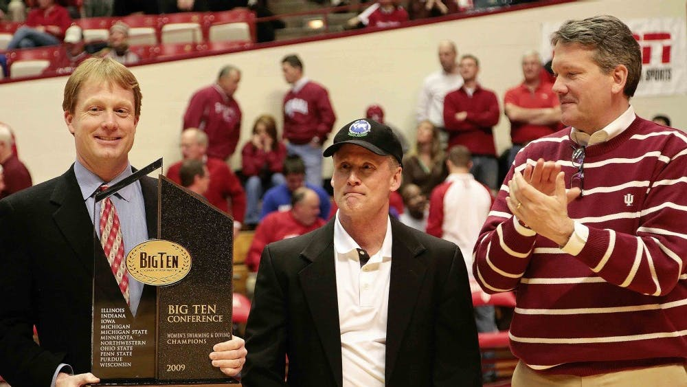 Athletic director Fred Glass, right, presents the Women's Big Ten Swimming and Diving Championship trophy to coaches Ray Looze, left, and Jeff Huber, center, during halftime of the Hoosiers 64-59 loss to No. 8 Michigan State March 6, 2009 night at Assembly Hall.