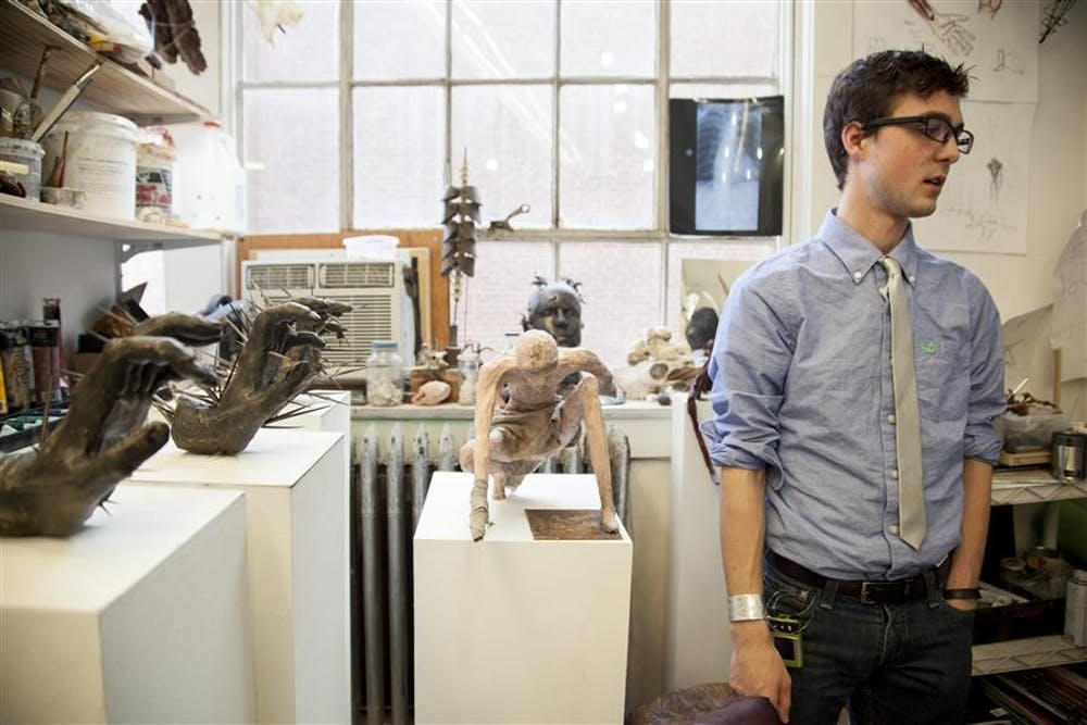 """<p>Senior Dillon Olney puts the final touches on his sculptures for his senior thesis show this month. Dillon has used his art to help him accept and cope with his diabetes. He wants his art to help others find """"Purpose of Pain.""""</p>"""