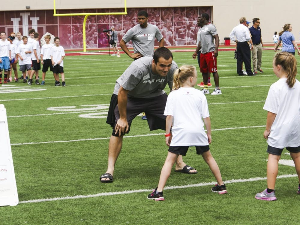 IU defensive end Nick Carovillano lines up across from a young girl about to run a route in the Change the Play event Tuesday in Bloomington.