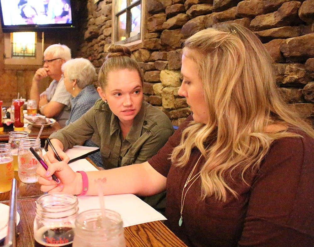 Lizzy Gentry and Samantha Geyer discuss answers at trivia night Thursday at Nick's English Hut. Proceeds from the trivia night benefit the Community Kitchen of Monroe County.