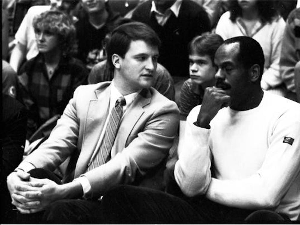 Former IU men's basketball assistant coaches Dan Dakich and Scott May talk on the bench Dec. 13, 1986, during a game against East Carolina University at Simon Skjodt Assembly Hall.Correction: a previous version of this caption incorrectly identified an assistant coach. The IDS regrets the error.