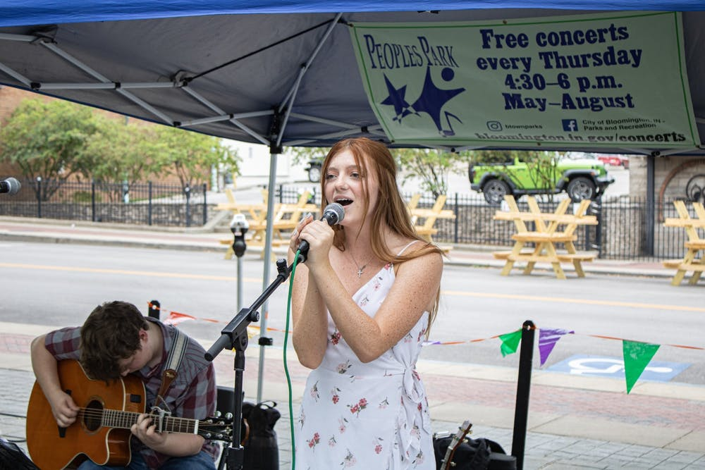 <p>Olivia Doyle sings as Derrick Weidner plays the guitar at Peoples  Park on May 27. Musical duo Carnes &amp; Shew will perform a free concert at People's Park on Thursday night.</p>